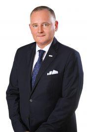 Zdjęcie Radnego Sejmiku Wojewódzkiego Roberta Bondyry. Postać ubrana w ciemnogranatowy garnitur, białą koszulę i niebieski krawat.