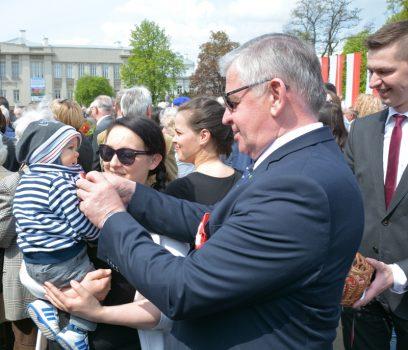 Marszałek województwa lubelskiego, Sławomir Sosnowski, przypina mieszkańcom biało-czerwone kokardki.