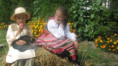 Dzieci w tradycyjnych strojach siedzą na sianie