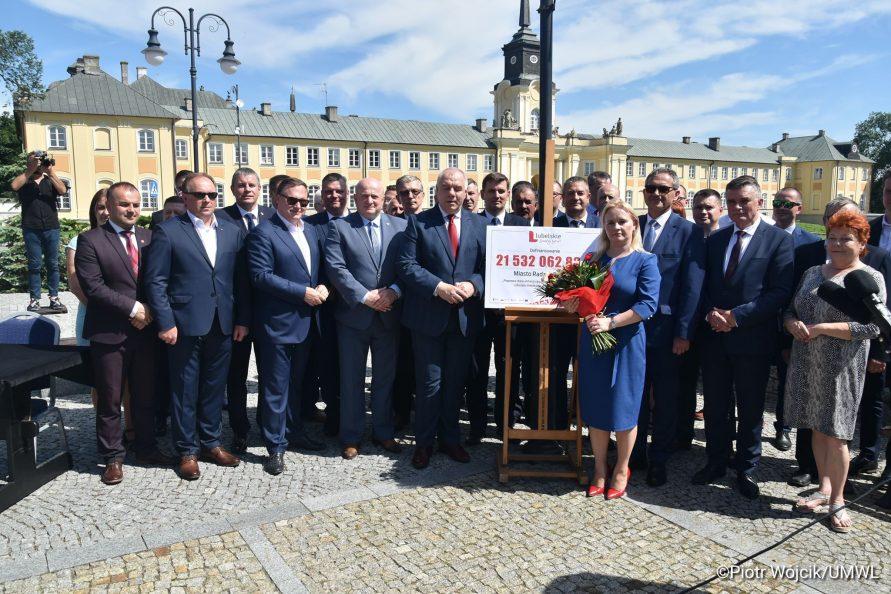 Grupowe zdjęcie po podpisaniu umowy na rewitalizację Zespołu Pałacowego Potockich w Radzyniu Podlaskim. W tle Pałac Potockich.