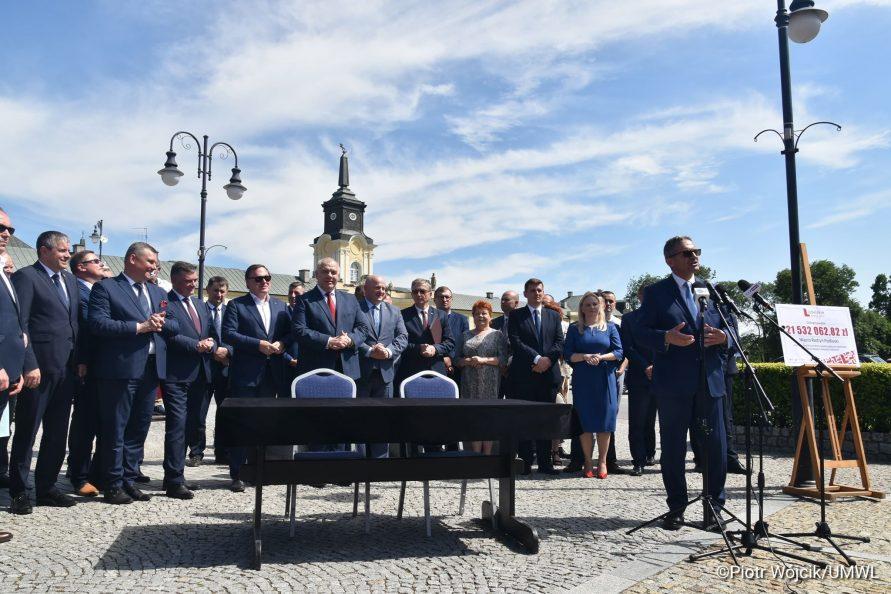 Podpisanie umowy na rewitalizację Zespołu Pałacowego Potockich w Radzyniu Podlaskim. Przy mikrofonach stoi Burmistrz Radzynia Podlaskiego Jerzy Rębek. W tle grupa ludzi uczestnicząca w podpisaniu umowy.