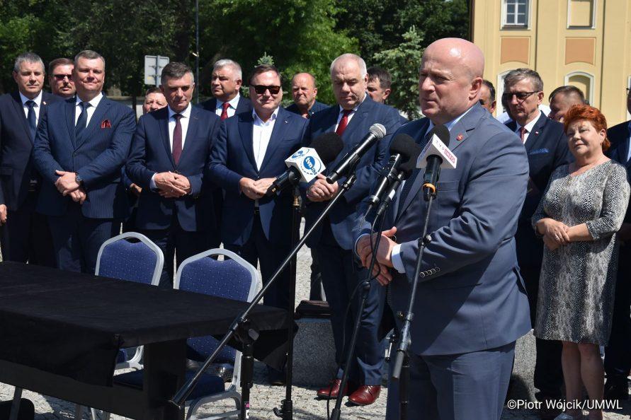 Podpisanie umowy na rewitalizację Zespołu Pałacowego Potockich w Radzyniu Podlaskim. Przy mikrofonach stoi Marszałek Województwa Lubelskiego Jarosław Stawiarski. W tle grupa ludzi uczestnicząca w podpisaniu umowy.