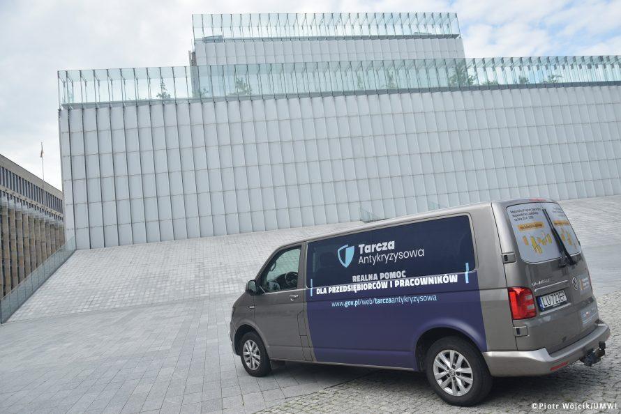 Oznakowany bus Mobilnego Punktu Informacyjnego stojący na Placu Teatralnym przed Centrum Spotkania Kultur