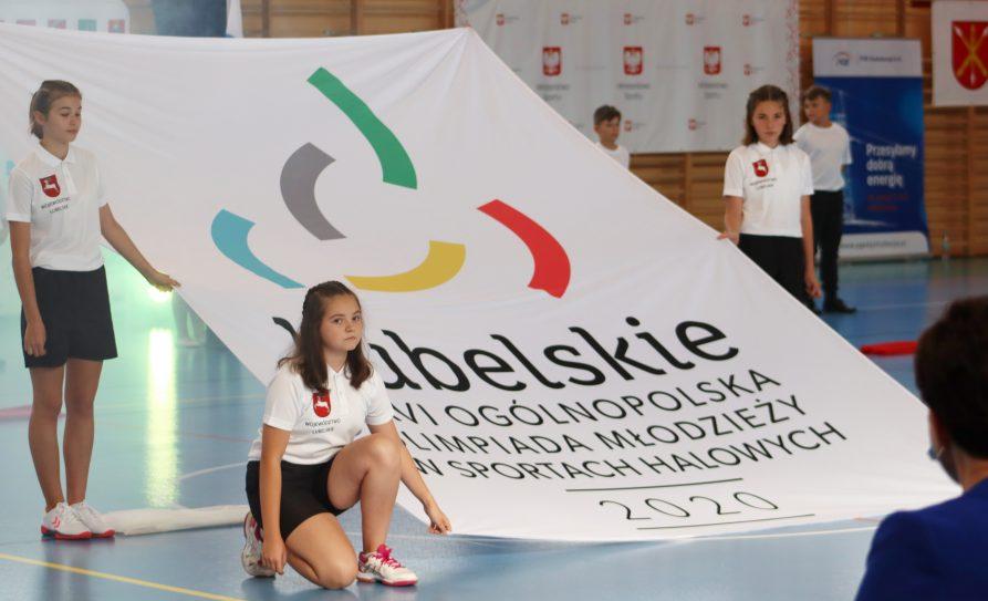 zdjęcie przedstawia uczestników olimpiady z flagą i logiem olimpiady