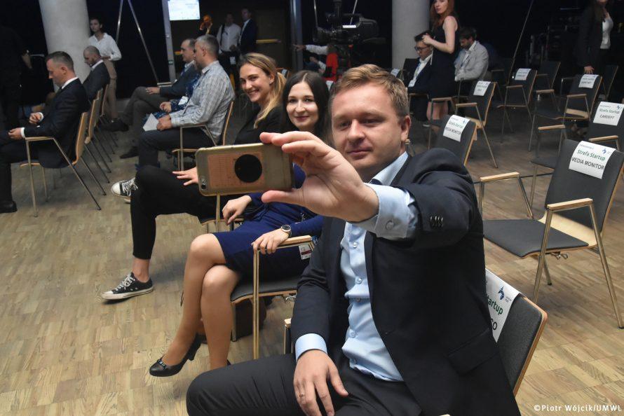 """Uczestnicy wydarzenia DemoDay w trakcie robienia tzw """"selfie""""."""