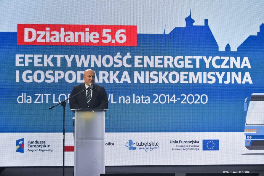 Marszałek Jarosław Stawiarski przy mównicy. W tle grafika działania 5.6 efektywność energetyczna i gospodarka niskoemisyjna.