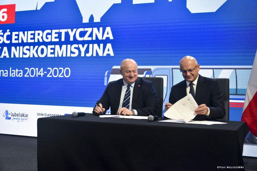 Przy stole umowy podpisują marszałek Jarosław Stawiarski i prezydent Krzysztof Żuk. W tle grafika działania 5.6 efektywność energetyczna i gospodarka niskoemisyjna.