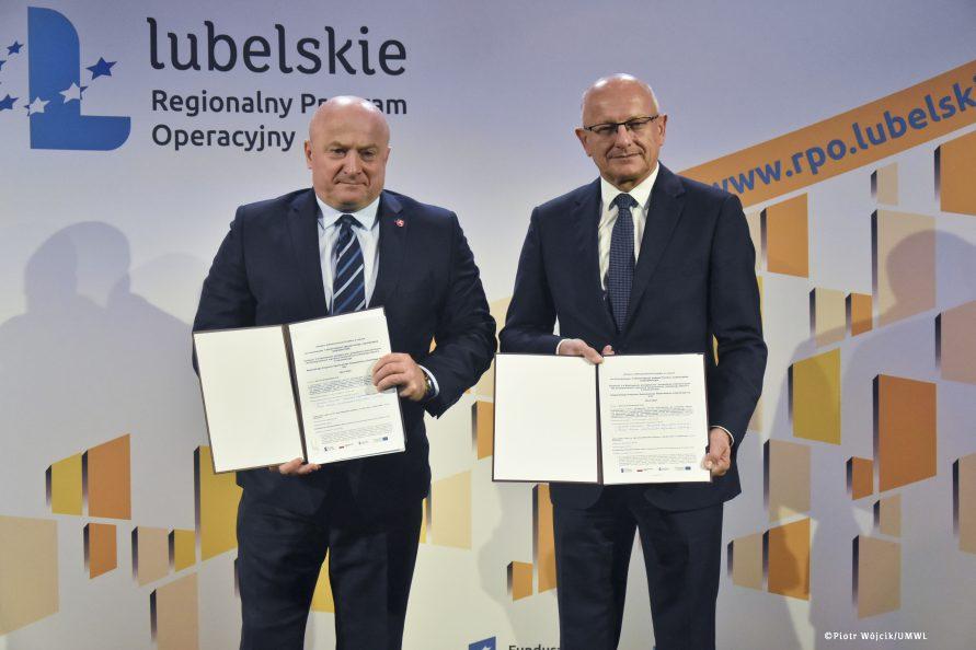Marszałek Jarosław Stawiarski i prezydent Krzystof Żuk pozują do zdjęcia trzymając otwarte teczki z podpisanymi umowami.