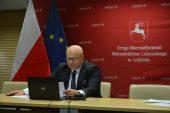 Marszałek Stawiarski siedzi przed komputerem, trzymając kartkę z przemówieniem. w tle czerwona ścianka z herbem województwa i napisem urząd marszałkowski województwa lubelskiego. po lewej od marszałka stoją flagi polski i unii europejskiej