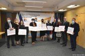 Grupowe zdjęcie beneficjentów z marszalkiem. Wszyscy beneficjenci trzymają symboliczne czeki z wypisanymi kwotami dofinansowania.