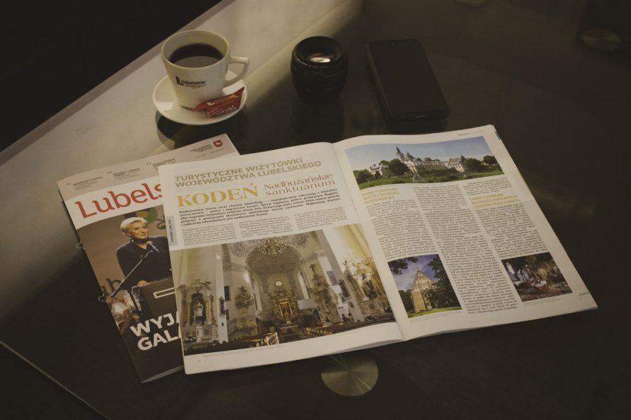 Dwa egzemplarze gazety lubelskie, jeden rozłożony przykrywa okładkę drugiego, leżą na szklanym blacie w towarzystwie telefonu, obiektywu, i filiżanki z kawą