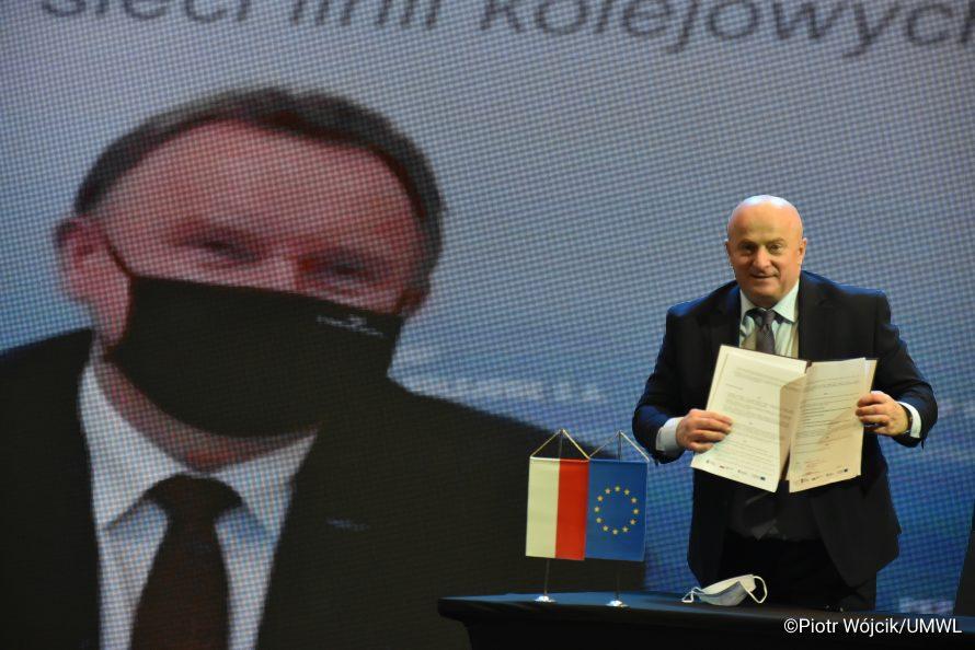 Marszałek Stawiarski prezentuje podpisaną umowę. W tle na ekranie postać prezesa PKP PLK S.A.