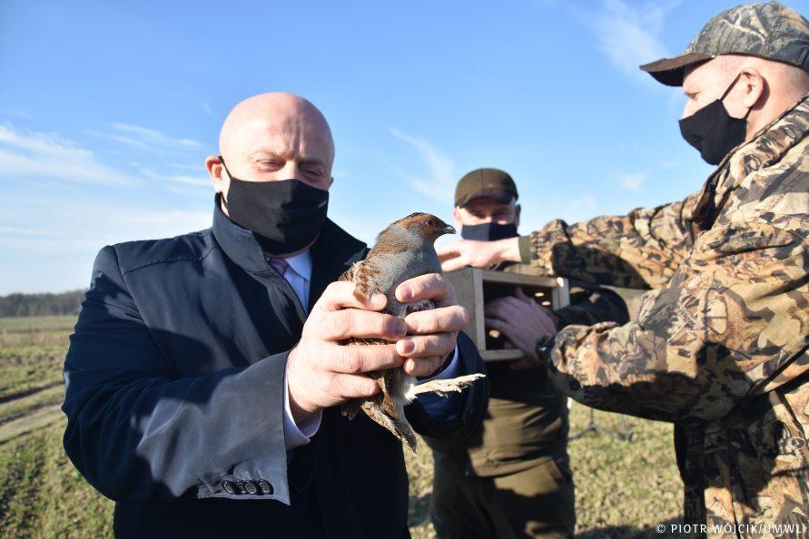 Marszałek Stawiarski (z lewej) trzyma w rękach kuropatwę. Z prawej dwóch członków koła łowieckiego.
