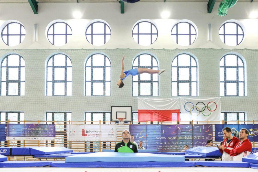 zawodnik podczas OOM w gimnastyce na trampolinie wykonujący ewolucje w powietrzu