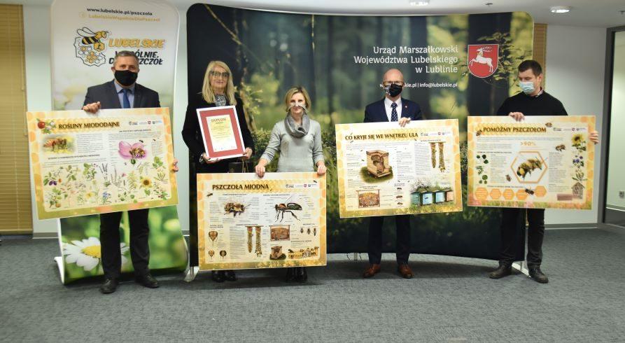 """Na zdjęciu widać pięciu uczestników spotkania (reprezentantów organizatorów konkursu i dyrektor nagrodzonej szkoły), którzy trzymają w rękach duże tablice edukacyjne o tematyce pszczelej. W tle za nimi widać ściankę z przyrodniczą fotografią i napisem """"Urząd Marszałkowski Województwa Lubelskiego"""" oraz stand z logo kampanii """"Lubelskie – wspólnie dla pszczół"""""""