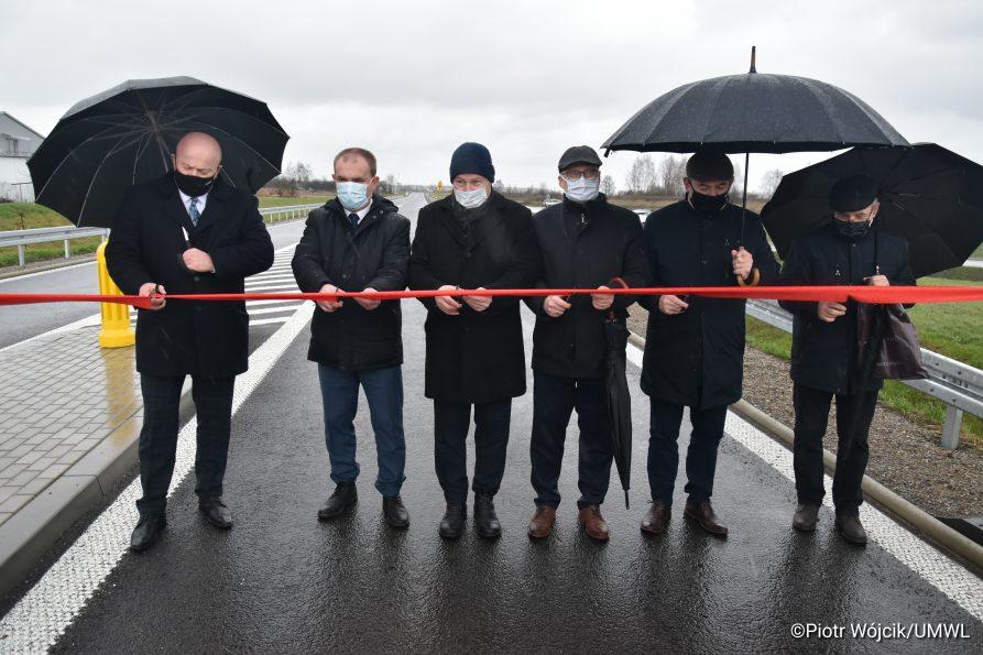 Od lewej Marszałek Jarosław Stawiarski, dyrektor zarządu dróg wojewódzkich Paweł Szumera oraz przedstawiciele samorządowców i wykonawców przecinają wstęgę.