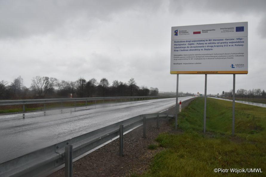 Widok na nową drogę i tablicę informującą o nazwie projektu współfinansowanego z Funduszy Europejskich