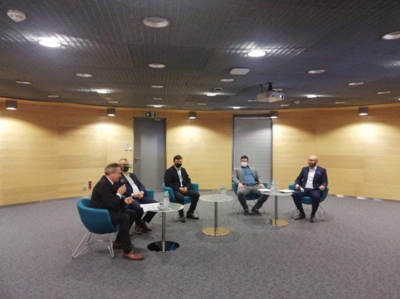 Uczestnicy forum siedzą w sali konferencyjnej