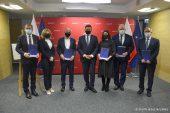 Na zdjęciu w szeregu stoi 7 osób, część z nich trzyma teczki z umowami, po środku stoi członek zarządu województwa Zdzisław Szwed