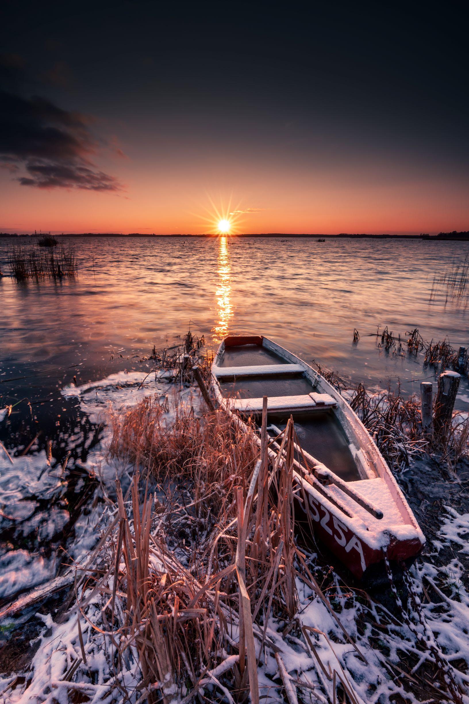 Zdjęcie przedstawia na pierwszym planie drewnianą łódkę przycumowaną do ośnieżonego brzegu jeziora. W tle widać zachodzące nad jeziorem słońce, a na samej górze granatowe, ciemne niebo.