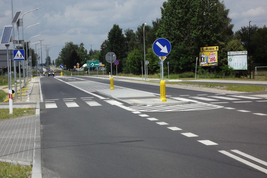 Widok na fragment drogi wojewódzkiej nr 812. Jezdnia z namalowanymi pasami, wysepką przez którą przeprowadzone jest przejście drogowe. W tle ciąg drzew. po obu stronach drogi widoczne są latarnie oraz znaki drogowe.