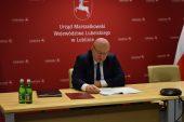 Przy stole nad dokumentami siedzi marszałek Stawiarski. W tle czerwona ścianka z herbem województwa i napisem Urząd Marszałkowski Województwa Lubelskiego w Lublinie.