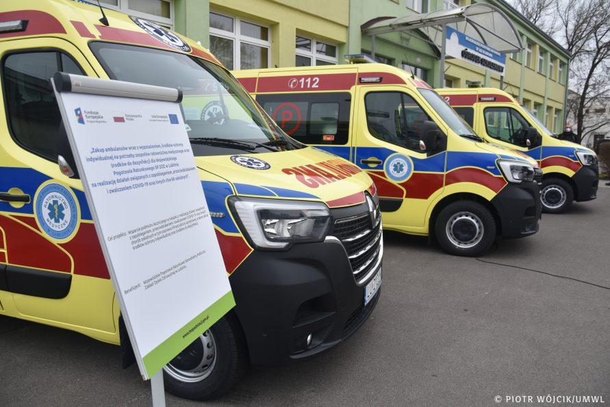 Trzy karetki pogotowia ratunkowego w żółtym malowaniu z niebiesko-czerwonymi pasami, ustawione jeden za drugim (widok na przód samochodów). W tle budynek Pogotowia Ratunkowego. Na pierwszym planie z lewej tablica z nazwą projektu unijnego.