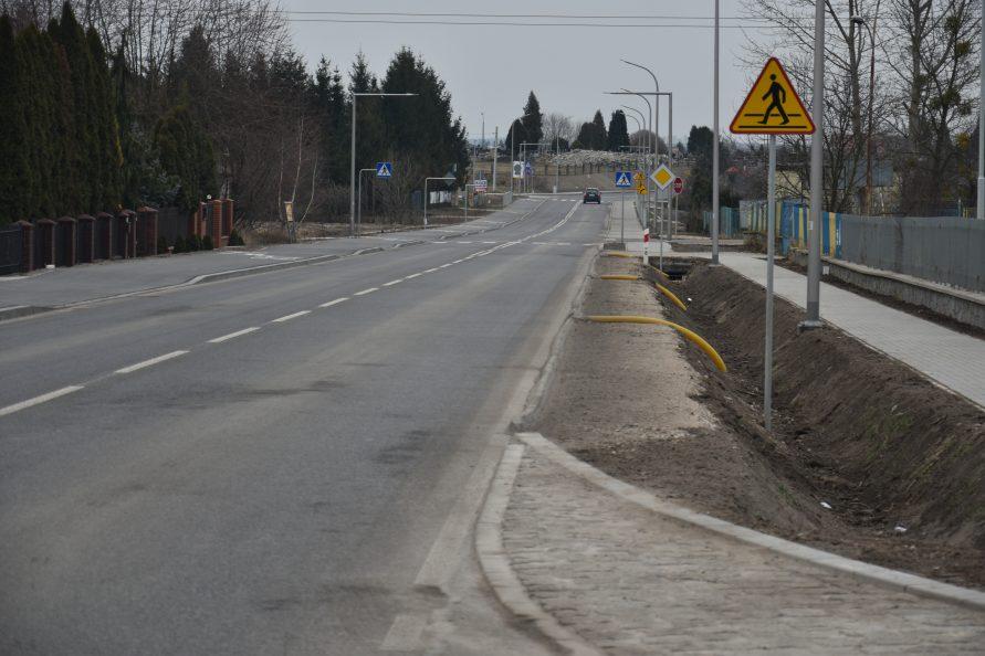 Widok na drogę, z prawej rów i chodnik oraz znak drogowy, po lewej szpaler drzew za ogrodzeniem.