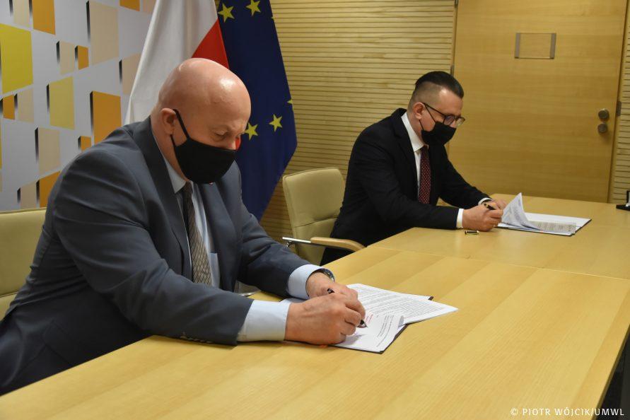 Przy stole siedzą od lewej marszałek Jarosław Stawiarski i prezydent Zamościa Andrzej Wnuk. Podpisują umowy na dofinansowanie.