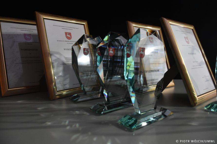 ramki z dyplomami i ozdobne szklane statuetki.