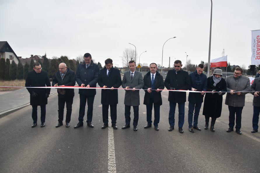 Uroczyste przecięcie wstęgi na drodze nr 837. Przy szarfie stoją przedstawiciele samorządów, wykonawców.