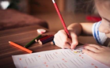 dziecko siedzące przy stole piszące w zeszycie czerwona kredką