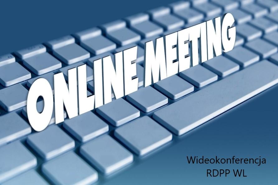 Obrazek o niebieskim tle z widocznymi klawiszami klawiatury komputera i napisem online meeting w srodkowej częsci zaś prawym dolnym roku napisem wideokonferencja RDPP WL