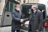 Przy otwartym bagażniku samochodu typu VAN podają sobie dłonie (od lewej) Konsul Generalny Ukrainy w Lublinie Vasyl Pavluk i wicemarszałek Zbigniew Wojciechowski. W środku samochodu widać pudełka ze sprzętem medycznym. W tle fragment ściany frontowej urzędu.
