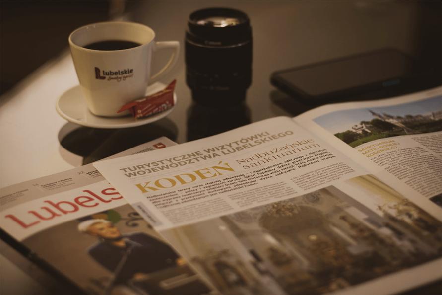 na zdjeciu otworzony magazyn Lubelskie.pl, pod nim widać okładkę danego numeru, nad nimi na szklanym stole stoi filiżanka kawy, obiektyw i telefon