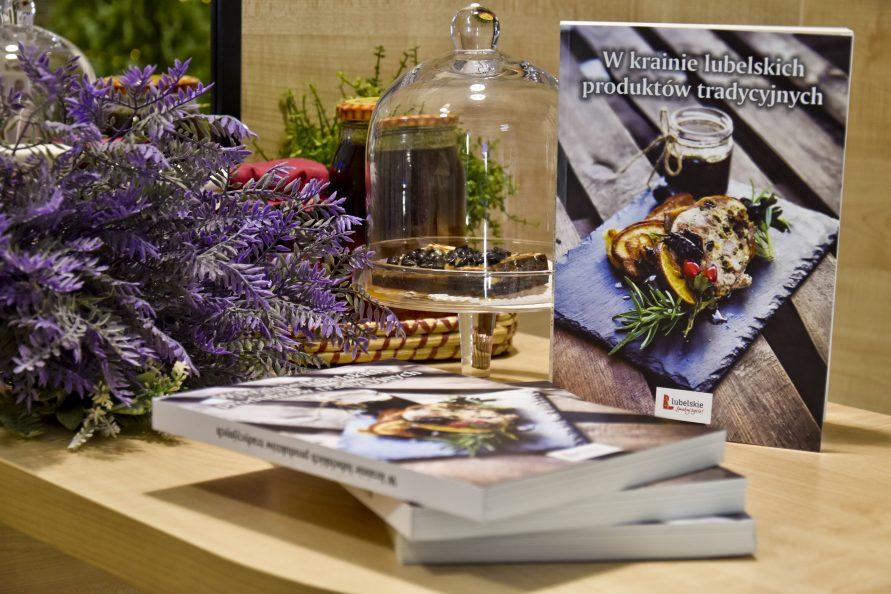 Na zdjęciu z prawej książka w Krainie lubelskich produktów tradycyjnych, przed nią leżą trzy książki ułozone jedna na drugą, z lewej szklana patera z kawałkiem czekolady oraz fioletowe rośliny