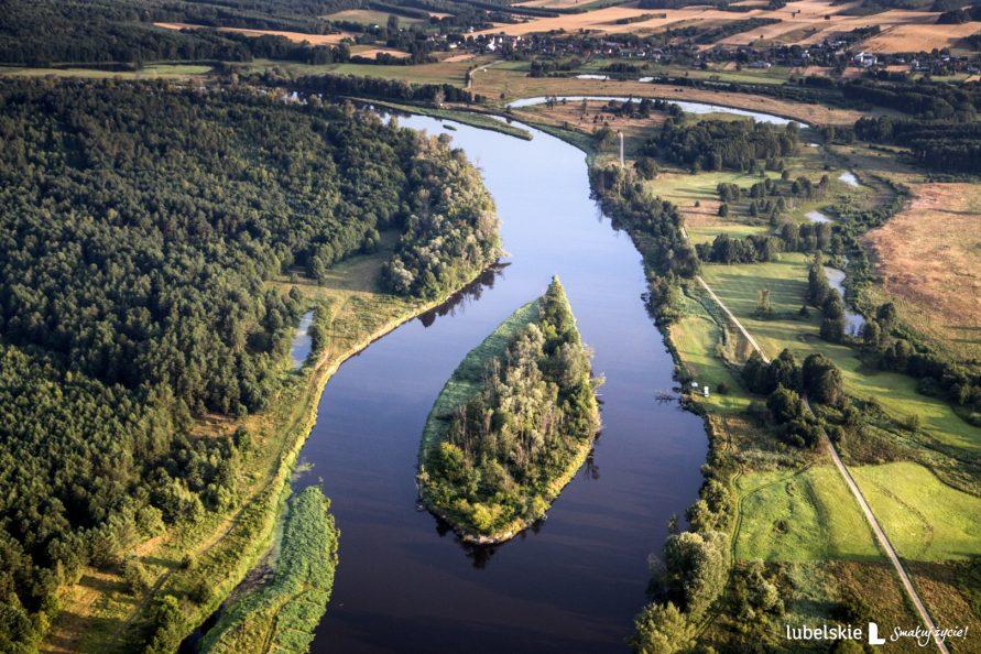 Widok z lotu ptaka na podlaski przełom Bugu. Po środku kadru fragment rzeki z wyspą, po obu stronach rzeki tereny zielone porośniete lasem, z prawej stronu widać drogę gruntową oraz meander rzeki. W górze kadru, w tle widać zabudowania i fragmenty pól