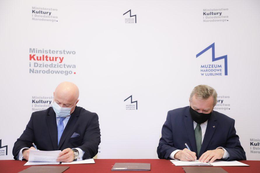 Z lewej marszałek Jarosław Stawiarski, z prawej minister kultury Piotr Gliński w trakcie podpisywania umowy w sprawie połączenia muzeum lubelskiego i muzeum narodowego w lublinie.
