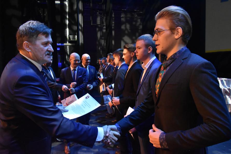 Z lewej członek zarządu Zdzisław Szwed wręcza dokument potwierdzający przyznanie stypendium jednemu z uczniów. w tle w rzędzie stoją inni stypendyści