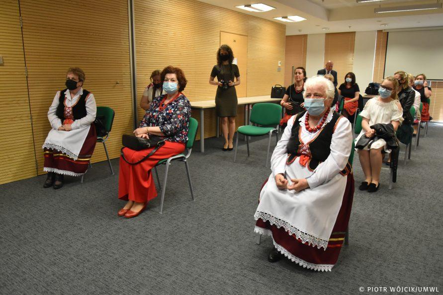 Na krzesłach, z zachowaniem odstępu siedzą laureatki konkursu. Część z nich ubrana jest tradycyjne stroje ludowe