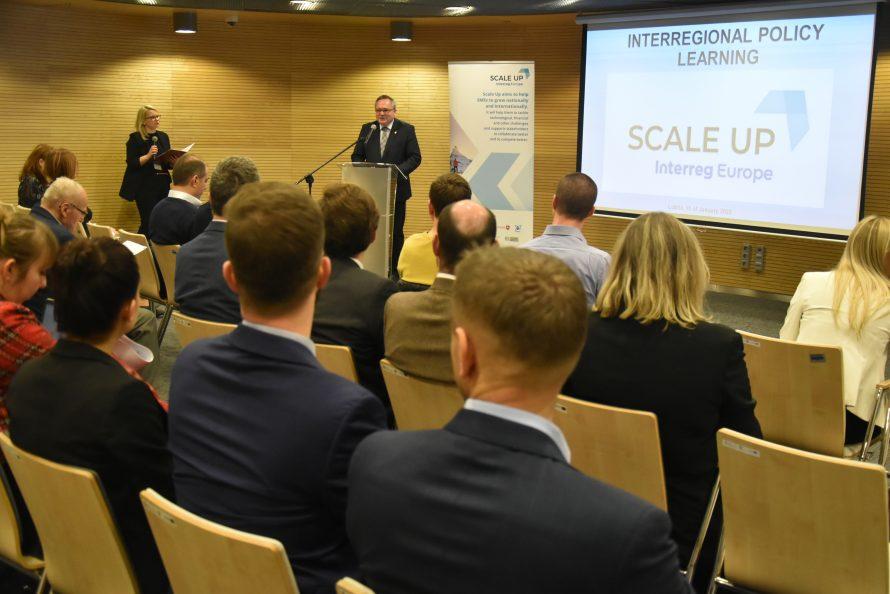 Na zdjęciu uczestnicy wydarzenia zwróceni w kierunku ekranu wyświetlajacego logo Scale Up i mównicy, przy której stoi wicemarszałek Wojciechowski