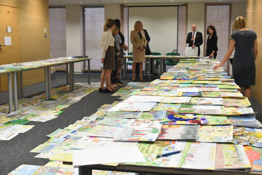 no staołach i podłodze rozłozone są prace plastyczne uczestników konkursu, w tle komisja konkursowa przyglądająca się pracom