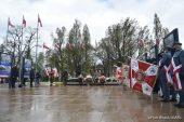 Z prawej poczty sztandarowe z pochylonymi sztandarami, w głębi zdjęcia grób nieznanego żołnierza, na którym znajdują się wiązanki i wieńce, za nim na masztach powiewają flagi Polski, w tle drzewa.