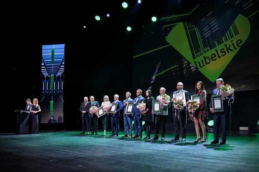 na scenie CSK stoją wyróżnieni tytułem marka lubelskie. Za nimi wyświetlone logo marka lubelskie, z lewej strony kadru, przy mównicy para prowadzących uroczystość