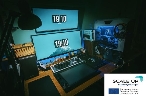 logo projektu SCALE-up na tle komputerów na biurku
