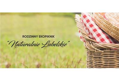 """Zdjęcie pokazuje zieloną łąkę (rozmytą), z prawej w polu ostrości kosz piknikowy z wilkiny z serwetą w biało-czerwoną kratę. Po środku czarny napis w dwóch wersach """"Rodzinny ekopiknik Naturalnie Lubelskie"""""""