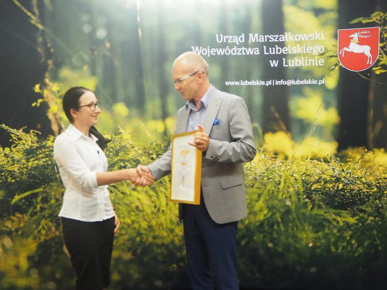 Członek zarządu Sebastian Trojak (z prawej) wręcza nagrodę laureatce konkursu instagramowego za miesiąc czerwiec. W tle ścianka przedstawiająca las. W górnym prawym rogu logotyp Urzędu Marszałkowskiego.