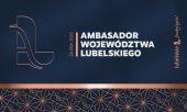 Grafika w tonacji granatowo złotej, z lewej ozdobna litera L z wpisaną literą A, po środku biały napis w trzech wersach Ambasador Województwa Lubelskiego