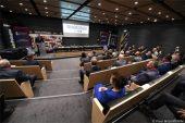 Widok na salę konferencyjną. na siedzeniach (tyłem do aparatu) siedzą uczestnicy konferencji. Z lewej przy mównicy na tle ścianki z logotypami sponorów Touru stoi prowadzący. Po środku stół prezydialny, nad nim ekran wyświetlający logo 78. Tour De Pologne