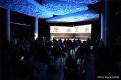 Widok na salę na której siedzą uczestnicy wydarzenia Gala Zakup Prospołeczny. Pomieszczenie wyciemnione, rozświetlony jest ekran wyświetlający logo ROPS i Zakup pro społeczny. Sufit podświetlony na niebiesko.